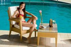 Muchacha que se sienta por la piscina Fotos de archivo libres de regalías