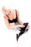Muchacha que se sienta que sostiene Tablet PC Imagen de archivo