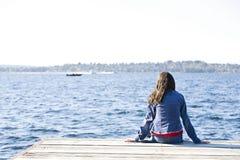 Muchacha que se sienta solamente en muelle por el lago imagen de archivo