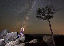 Muchacha que se sienta solamente encima del canto rodado enorme en la postura del loto que hace yoga debajo del cielo estrellado  imagen de archivo libre de regalías