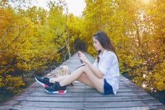Muchacha que se sienta solamente y mano que sostiene la cámara en el bridg de madera Foto de archivo libre de regalías
