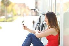 Muchacha que se sienta usando un teléfono móvil en un parque Fotos de archivo libres de regalías