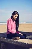 Muchacha que se sienta y que piensa en la playa Fotografía de archivo libre de regalías