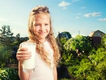 Muchacha que se sostiene de cristal con leche Imagen de archivo