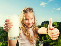 Muchacha que se sostiene de cristal con leche Fotos de archivo libres de regalías