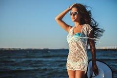 Muchacha que se sostiene el pelo mientras que se coloca en una playa ventosa imagen de archivo libre de regalías