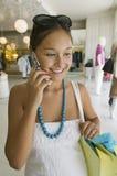 Muchacha que se sostiene usando el teléfono celular en tienda de ropa Fotografía de archivo