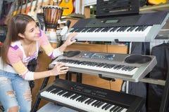 Muchacha que selecciona el sintetizador en tienda de la música Fotografía de archivo