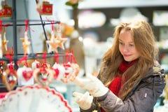 Muchacha que selecciona la decoración en un mercado de la Navidad Foto de archivo