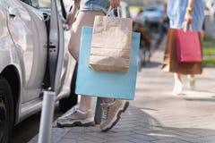 Muchacha que sienta en un coche con ella compras Foto de archivo