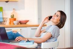 Muchacha que sienta hablar confortable en el teléfono Imagen de archivo libre de regalías