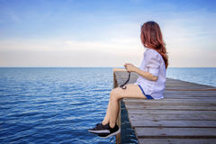 Muchacha que sienta solamente en el puente de madera en el mar foto de archivo libre de regalías