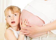 Muchacha que siente el vientre embarazada de su madre. Fotos de archivo libres de regalías