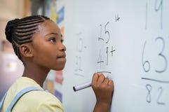 Muchacha que soluciona la adición matemática fotos de archivo