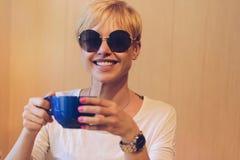 Muchacha que sonríe con café Imagen de archivo