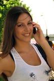 Muchacha que sonríe con hablar móvil Imágenes de archivo libres de regalías