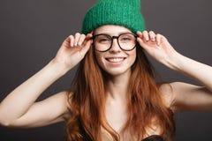 Muchacha que sonríe con los ojos cerrados que tocan su pelo rizado rojo sobre el fondo blanco Fotografía de archivo libre de regalías