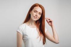 Muchacha que sonríe con los ojos cerrados que tocan su pelo rojo sobre el fondo blanco Imagen de archivo libre de regalías