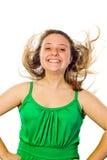 Muchacha que sonríe con su soplar del pelo Fotografía de archivo