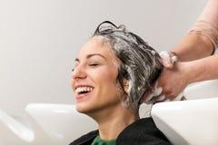 Muchacha que sonríe durante su pelo que es lavado fotos de archivo