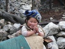 Muchacha que sonríe e inclinada en la pared - Nepal Imagenes de archivo