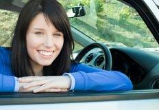 Muchacha que sonríe en la cámara que se sienta en su coche Imagenes de archivo