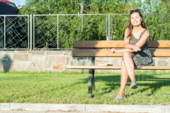 Muchacha que sonríe en sentarse que lleva del parque en banco Foto de archivo
