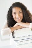 Muchacha que sonríe mientras que se inclina en los libros apilados en sala de clase Foto de archivo libre de regalías