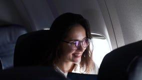 Muchacha que sonríe mientras que se sienta en el avión almacen de video