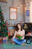 Muchacha que sonríe, sentándose y presentando en la tela escocesa con la caja de regalo a disposición Fotos de archivo libres de regalías