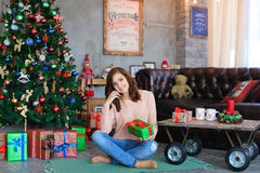 Muchacha que sonríe, sentándose y presentando en la tela escocesa con la caja de regalo a disposición Fotos de archivo