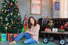 Muchacha que sonríe, sentándose y presentando en la tela escocesa con la caja de regalo a disposición Imagen de archivo libre de regalías