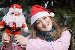 Muchacha que sonríe sosteniendo la muñeca de Santa Fotos de archivo libres de regalías