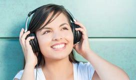 Muchacha que sonríe y que disfruta de su música en los auriculares Foto de archivo