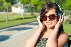 Muchacha que sonríe y que disfruta de su música en los auriculares Imagen de archivo