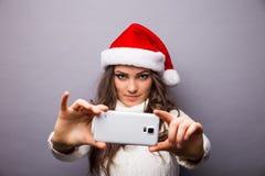 Muchacha que sonríe y que hace el selfie en el teléfono móvil Foto de archivo libre de regalías