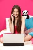 Muchacha que sonríe y que hace una llamada en su sitio rosado Foto de archivo libre de regalías