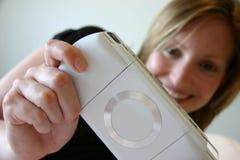 Muchacha que sonríe y que juega la consola handheld del juego Imagenes de archivo