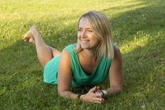 Muchacha que sonríe y que miente en la hierba Imágenes de archivo libres de regalías
