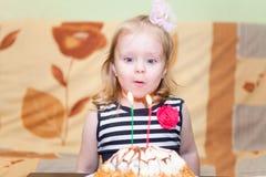 Muchacha que sopla dos velas en la torta de cumpleaños Fotografía de archivo