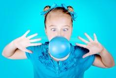 Muchacha que sopla el chicle de globo azul Imágenes de archivo libres de regalías