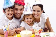 Muchacha que sopla hacia fuera velas en el día de su cumpleaños Fotos de archivo libres de regalías
