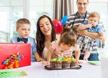 Muchacha que sopla hacia fuera velas en la torta de cumpleaños Fotos de archivo libres de regalías