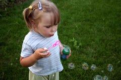 Muchacha que sopla los bubles del jabón Imagenes de archivo