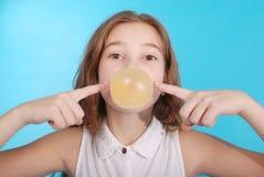Muchacha que sopla una burbuja grande del chicle de globo Fotos de archivo libres de regalías