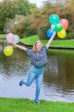 Muchacha que soporta muchos globos en la charca Imagen de archivo libre de regalías