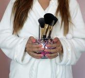 Muchacha que sostiene cepillos del maquillaje Imagen de archivo libre de regalías