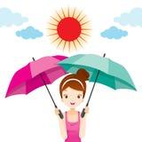 Muchacha que sostiene dos paraguas con la luz de Sun Imagen de archivo libre de regalías
