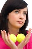 Muchacha que sostiene dos pelotas de tenis Foto de archivo libre de regalías