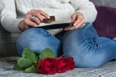 Muchacha que sostiene el caramelo y la placa de chocolate en manos en rodillas y rosas rojas imagenes de archivo